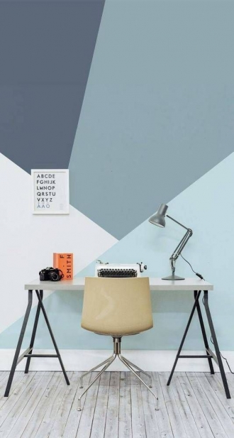 Desk with geometric blue wallpaper in room